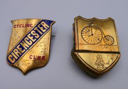 A brass and enamel decorated Cirencester Cycling Club badge and a brass clip decorated with a penny