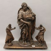 A 17th century carved wooden model of an apostle and two carved wooden angels,