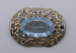 An 835 silver brooch centred with a blue stone, possibly aquamarine.
