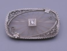 A 14 ct white gold oblong crystal back brooch with solitaire diamond centre. 3 cm wide.