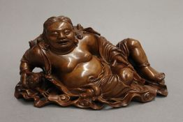 A 19th century Chinese wood carving of a reclining buddha. 26 cm wide.