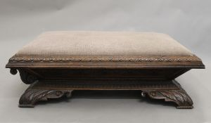 A large Victorian carved oak footstool (converted). 132 cm long.