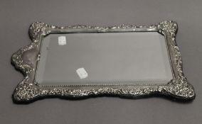 A silver framed mirror. 38 cm high.