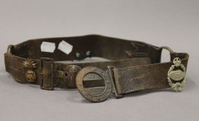 A vintage Boy Scouts leather belt set with military cap badges. 82 cm long.