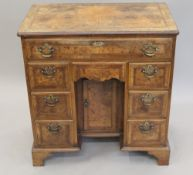 An 18th century style walnut knee hole desk. 75 cm wide.