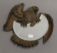 A 19th century Blackforest mirror formed as an eagle. 25 cm wide.