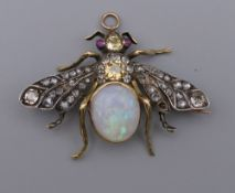 An unmarked gold diamond, opal and ruby brooch formed as a fly. 4.5 cm wide. 10.