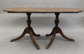 A modern mahogany twin pedestal dining table, with single leaf. 212 cm long.