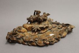 A Blackforest carved wooden desk stand depicting two hares. 37 cm wide.