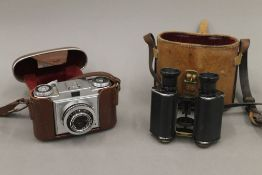 A cased set of binoculars and a Zeiss Ikon camera. The former 13 cm high.
