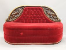 A Victorian carved walnut red velvet upholstered settee. 156 cm wide.