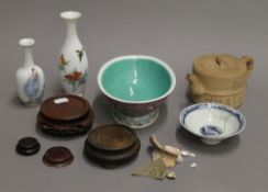 Two Chinese vases, two bowls, a teapot and wooden stands.