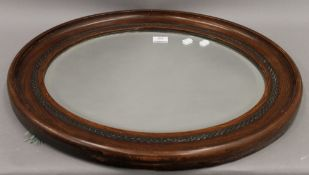An early 20th century oval wall mirror. 63.5 cm wide.