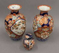 A pair of 19th century Japanese Imari decorated vases together with an Imari tea caddy.