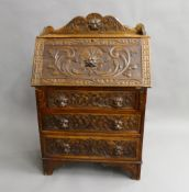 A Victorian carved oak bureau. 80 cm wide.