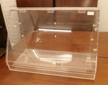 A perspex display case. 60.5 cm wide, 40.5 cm high, 30 cm deep.