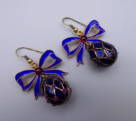 A pair of enamel decorated egg form earrings. 3 cm high.