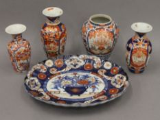 Five 19th century Japanese Imari porcelain items; comprising of an oval platter and four vases.