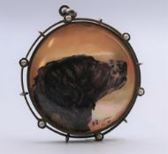 A framed painted mother-of-pearl pendant decorated with a dog. 3.5 cm diameter.