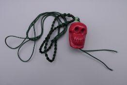 A coral skull pendant. 3 cm high.