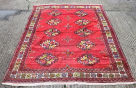 A red ground rug. 380 x 220 cm.