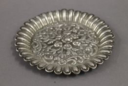 An Eastern embossed white metal pin tray. 11.5 cm diameter. 2.7 troy ounces.