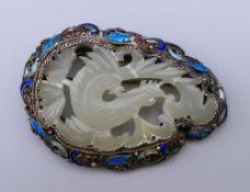 A silver, jade and enamel brooch. 5.5 cm wide.