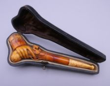 A cased 19th century meerschaum and amber pipe formed as a hand holding a pistol. 12 cm long.