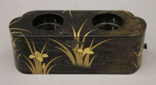 A Japanese Meiji Period lacquered travelling wine cup rest and five white metal wine cups.