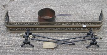 A brass fender, fire irons and a copper pan.