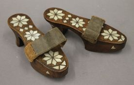 A pair of Eastern mother-of-pearl and unmarked white metal inlaid ladies shoes. 23 cm long.