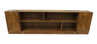 An early 20th century Art Deco walnut bookcase. 240 cm long, 70 cm high, 29.5 cm deep.