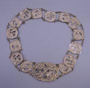 A Japanese silver belt. 66 cm long.