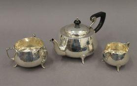 An Arts & Crafts beaten silver three-piece tea set. The teapot 25 cm long. 23.