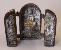 An Oriental bronze triptych. 14 cm high.