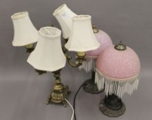 A pair of table lamps and another.