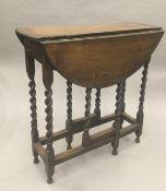 A small oak barley twist gate leg table. 24 cm wide closed.