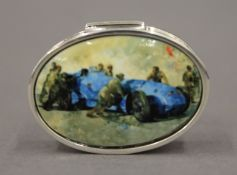 An oval silver box decorated with a racing car. 3.75 cm wide.