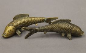 A pair of Oriental cast brass models of carp, with butterfly character marks to base.