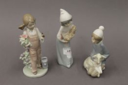 Three Lladro figures. The largest 19.5 cm high.