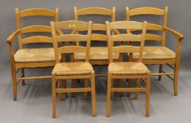 Three oak open arm chairs with rush seats and two rush seated side chairs. The former 58 cm wide.