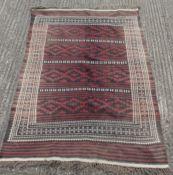 A black, maroon and cream rug. 140 x 195 cm.