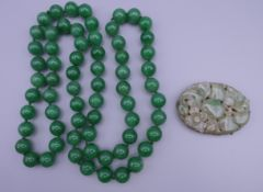 A string of apple green jade beads and a vintage carved jade brooch with silver mount stamped,