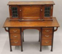 An Arts and Crafts walnut desk. 137 cm wide.