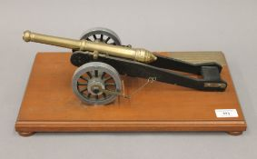A model canon on a wooden plinth,