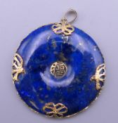 A Chinese 14 ct gold mounted lapis pendant. 3.5 cm diameter.