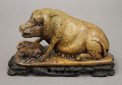 A Chinese soapstone carving of a sow and piglets, mounted on a wooden stand. 17 cm long overall.