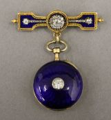 An 18 ct gold diamond and blue enamel brooch watch. 5 cm high.