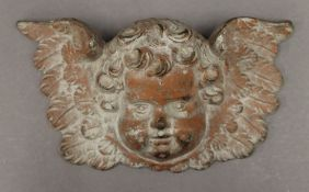 A Victorian cast iron cherub mask. 24 cm wide.