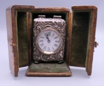 A silver cased carriage clock, housed in a leather travelling case. The case 10 cm high.